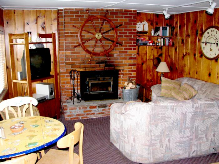 Anchor's Away living room with dining table and wood stove